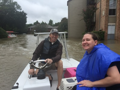 Andrew White and a Woman Smile in His Rescue Boat in a Flooded Area