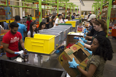 Houston Food Bank volunteers sort donations at preparation stations in the Food Bank warehouse during Hurricane Harvey recovery