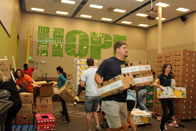 Greg Mancz, a professional football player for the Houston Texans, moves boxes of donated fruit through the Houston Food Bank warehouse during Hurricane Harvey recovery
