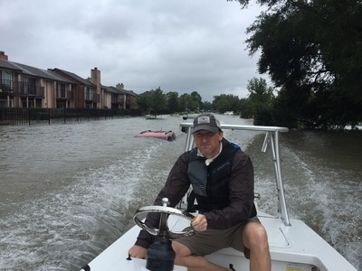 Andrew White Drives His Boat through a Flooded Area, Passing Several Flooded Cars
