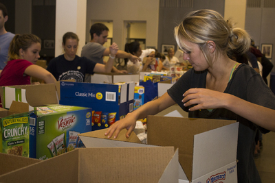 Houston Food Bank volunteer packs a disaster relief box at the Food Bank warehouse during Hurricane Harvey recovery