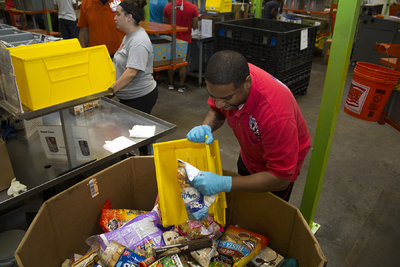 Houston Food Bank volunteer grabs a bag of marshmallows from a box of donations during Hurricane Harvey recovery